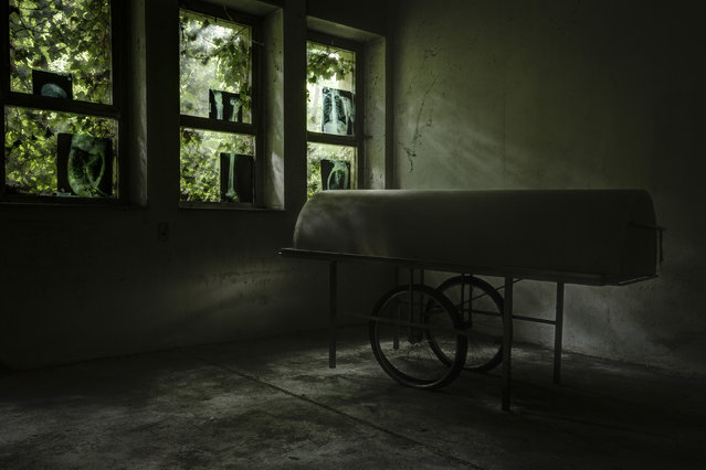 An operating bed lies in the shadows as x-rays litter the window. (Photo by Thomas Windisch/Caters News)