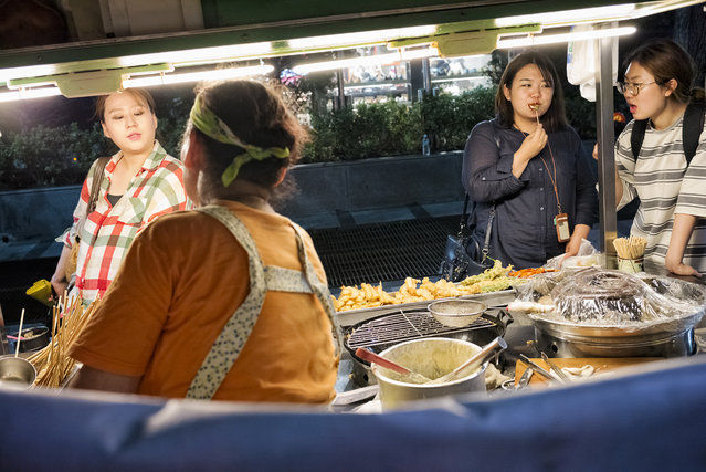 People enjoy street food at a food cart near Sinchon subway station on August 4, 2015 in Seoul, South Korea. (Photo by Shin Woong-jae/The Washington Post)