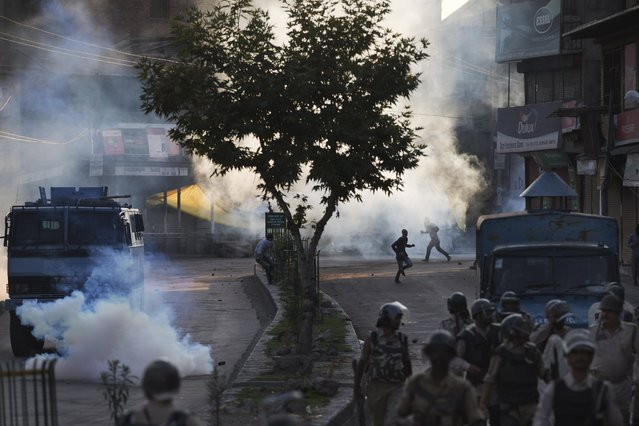 Kashmiri Muslim protesters run for cover amid tear gas smoke as Indian paramilitary soldiers walk back towards their base camp after a day long curfew in Srinagar, Indian controlled Kashmir, Monday, August 8, 2016. Kashmir has been under a security lockdown and curfew since the killing of a popular rebel commander on July 8 sparked some of the largest protests against Indian rule in recent years. (Photo by Dar Yasin/AP Photo)