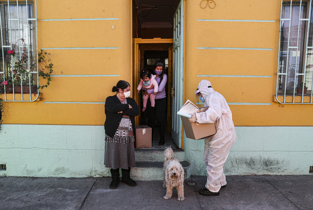 A city worker, dressed in protective gear, delivers a box of food during a mandatory quarantine ordered by the government amid the new coronavirus pandemic in Santiago, Friday, May 22, 2020. The Chilean government began delivery of 2.5 million boxes of food and cleaning products for vulnerable families. (Photo by Esteban Felix/AP Photo)