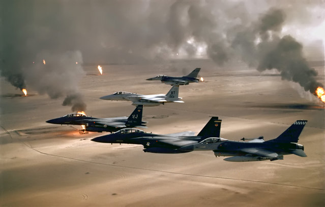 USAF aircraft of the 4th Fighter Wing (F-16, F-15C and F-15E) fly over Kuwaiti oil fires, set by the retreating Iraqi army during Operation Desert Storm in 1991. (Photo by USAF)