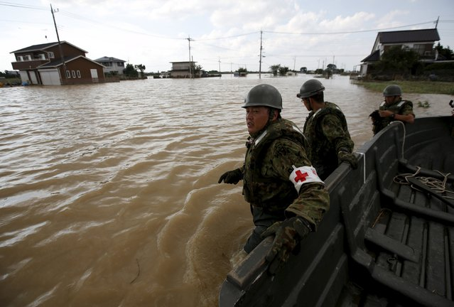 Japanese Self-Defence Force's 1st Infantry Regiment soldiers conduct a search and rescue operation at a residential area flooded by the Kinugawa river, caused by Typhoon Etau at Araigi town in Joso, Ibaraki prefecture, Japan, September 12, 2015. Search teams using boats and helicopters resumed looking on Saturday for at least 16 people still missing after torrential rain and flooding across Japan this week, while thousands waited to return to their homes as waters slowly receded. (Photo by Issei Kato/Reuters)