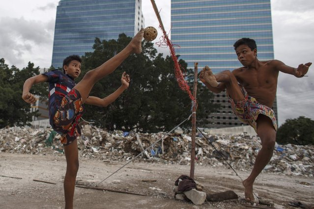 Migrant workers play sepak takraw in Bangkok September 17, 2014. The sport, native to Southeast Asia, sees players use any part of their bodies except their hands and arms to send a rattan ball into the opposing court. Thailand has dominated the sport since it was introduced at the 1990 Beijing Games, winning 18 of the 27 golds awarded. There are six golds on offer in this year's games, which are held in Incheon. (Photo by Athit Perawongmetha/Reuters)