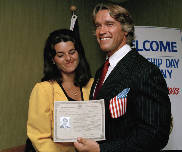 In this September 16, 1983 file photo, actor and bodybuilder Arnold Schwarzenegger shows off his new U.S. citizenship papers as Maria Shriver, daughter of Sargent and Eunice Shriver, looks on at the Shrine Auditorium in Hollywood, Calif. (Photo by Wally Fong/AP Photo)