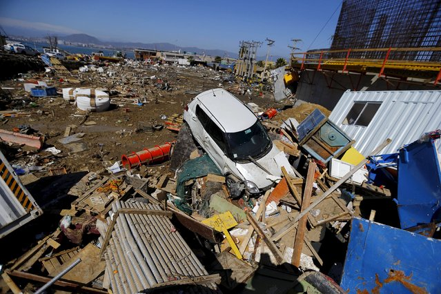 A damaged car lies on debris after an earthquake hit areas of central Chile, in Coquimbo city, north of Santiago, Chile, September 17, 2015. (Photo by Ivan Alvarado/Reuters)