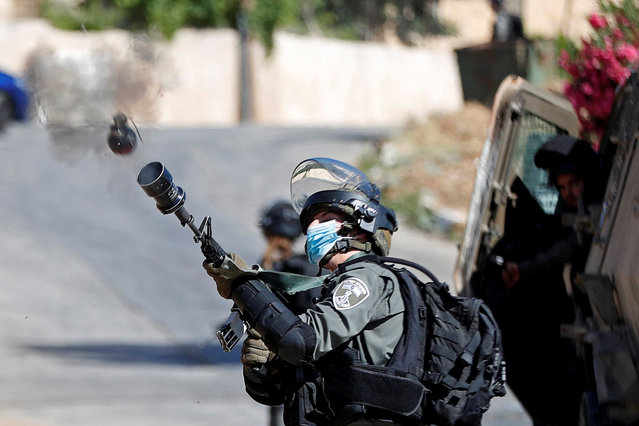 An Israeli border police member fires a tear gas canister towards Palestinians protesting against the demolition of a house under construction by Israeli forces, in Beitunia in the Israeli-occupied West Bank, June 24, 2020. (Photo by Mohamad Torokman/Reuters)