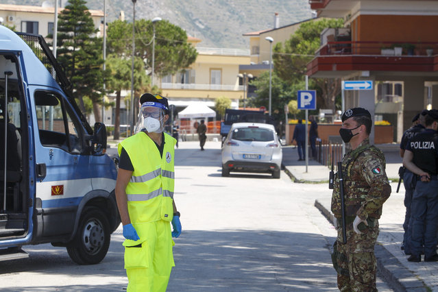 Civil protection and army officers stand at a road block in front of an apartment complex where dozens of COVID-19 cases have been registered among a community of Bulgarian farm workers, in Mondragone, in the southern Italian region of Campania, Friday, June 26, 2020. The governor of the region is insisting that the farm workers should stay inside for 15 days, not even emerging for food, and that the national civil protection agency should deliver them groceries. (Photo by Riccardo De Luca/AP Photo)