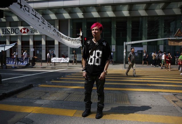 "Joe Chan, 30, a shop owner and Mongkok resident, poses on Nathan Road in Mongkok shopping district, Hong Kong October 7, 2014. Chan said, ""I don't care much about politics, but the local government tilting toward China is not good for Hong Kong. I come out because I am against the use of teargas by the police over non-violent protests"". (Photo by Bobby Yip/Reuters)"