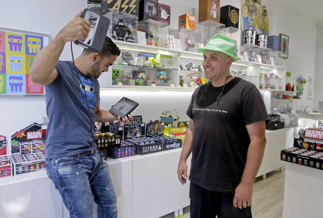 In this August 14, 2014 photo, Victor De Los Angeles, left, owner of Cubo toy store, demonstrates the use of the Sense 3D scanner on coffee shop owner Kevin Micelli at his store in New York. With the old studio portrait supplanted by the selfie, 3-D scanning services provide a new reason for people to go to a store and stand stock-still in front of a camera. (Photo by Julie Jacobson/AP Photo)