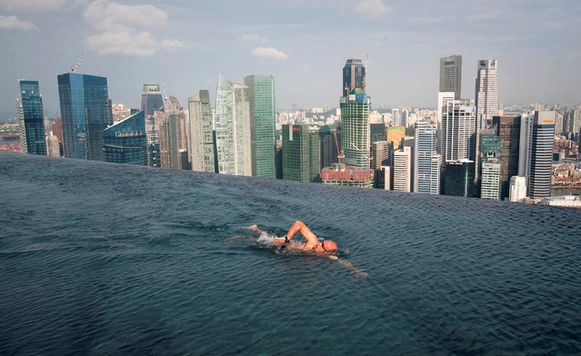 A guest swims in the infinity pool of the Skypark that tops the Marina Bay Sands hotel towers in Singapore June 24, 2010. (Photo by Vivek Prakash/Reuters)