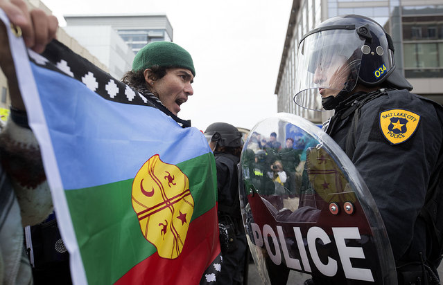 Anthony Fierro yells in front of a police officer as protesters are stopped from marching up State Street during President Donald Trump's announcement to eliminate vast portions of Utah's Bears Ears and Grand Staircase-Escalante national monuments in Salt Lake City, Utah, on Monday, December 4, 2017. (Photo by Laura Seitz/The Deseret News via AP Photo)