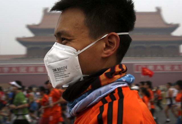 A runner, wearing a mask to protect himself from pollutants, jogs past Tiananmen Gate shrouded in haze while taking part in the 2014 Beijing International Marathon in Beijing, China Sunday, October 19, 2014. (Photo by Andy Wong/AP Photo)