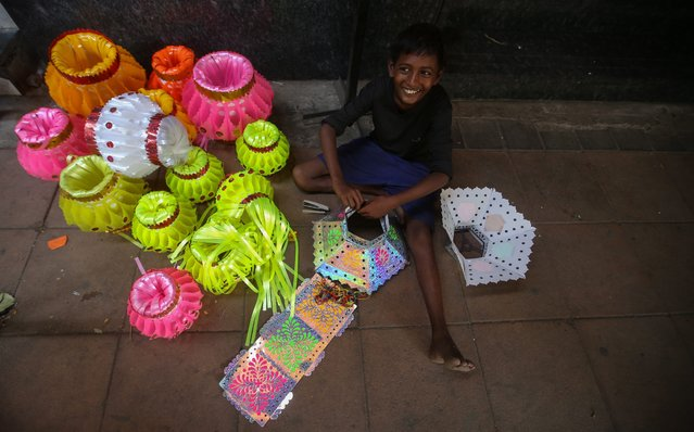 An Indian boy makes colorful laterns at a market ahead of the Diwali festival in Mumbai, India, 21 October 2014. (Photo by Divyakant Solanki/EPA)