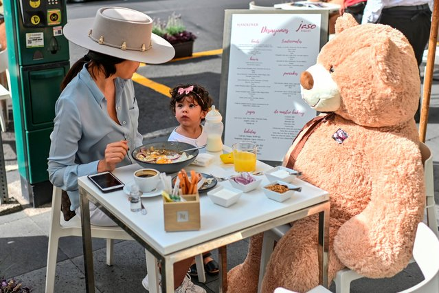 Customers sit with a teddy bear used to keep social distancing measures, during the gradual reopening of commercial activities amid the novel coronavirus pandemic, at a restaurant in Polanco neighborhood, in Mexico City, on July 26, 2020. (Photo by Pedro Pardo/AFP Photo)