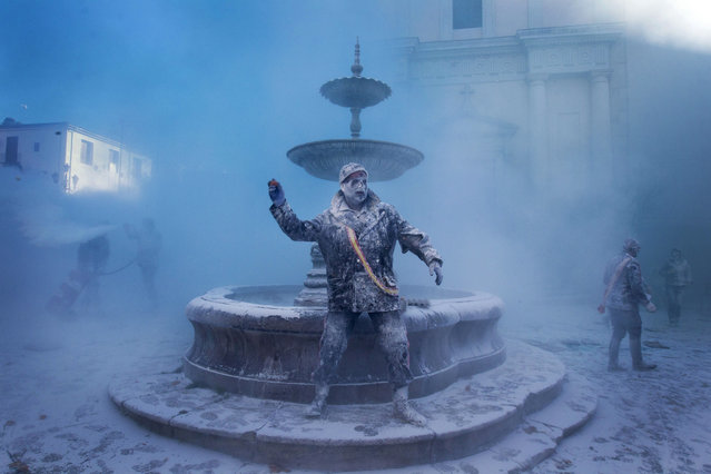 """A military dressed man throws an egg as he takes part in the battle of """"Enfarinats"""", a floor fight in the town of Ibi, in the south-eastern Spain on December 28, 2012. For 200 years Ibi's citizens annually celebrate with a battle using flour, eggs and firecrackers outside the city townhall.   (Photo by Jaime Reina)"""