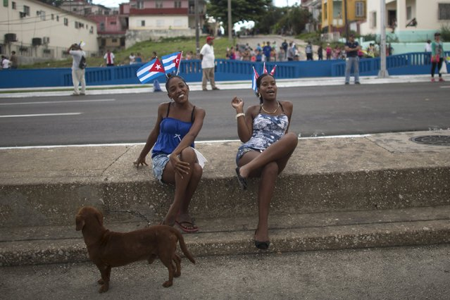 Women react to the camera as they wait for the arrival of Pope Francis from the airport in Havana September 19, 2015. (Photo by Alexandre Meneghini/Reuters)