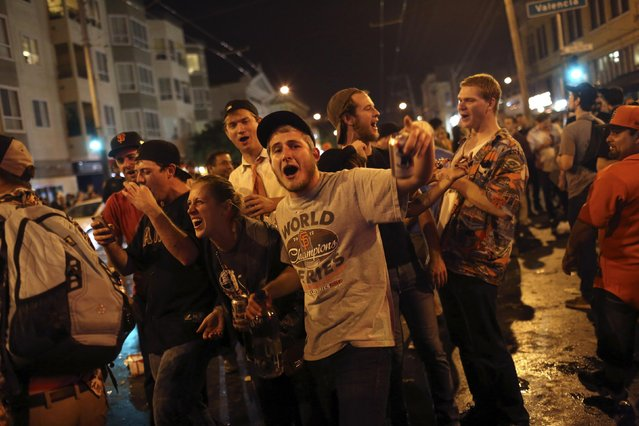 Fans celebrate in the street in the Mission District after the San Francisco Giants defeated the Kansas City Royals in Game 7 of the World Series, in San Francisco, California October 29, 2014. (Photo by Robert Galbraith/Reuters)