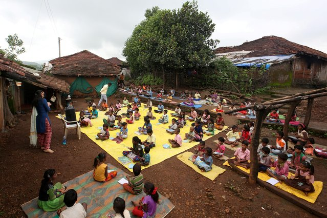 Children, who have missed their online classes due to a lack of internet facilities, maintain a safe distance as they listen to pre-recorded lessons over loudspeakers after schools were closed following the coronavirus outbreak, in Dandwal village in the western state of Maharashtra, India, July 28, 2020. (Photo by Prashant Waydande/Reuters)