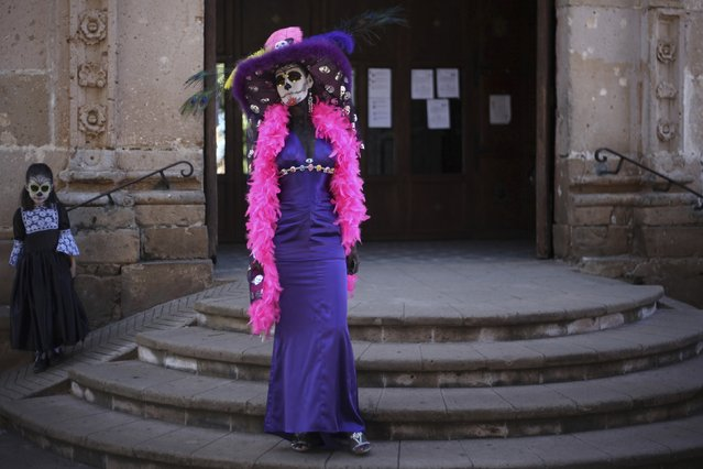 """People, with their faces painted as skulls, pose for a photo during the start of the """"Las Catrinas"""" festival,  ahead of the Day of the Dead in Cupula on the outskirts of Morelia, October 26, 2014. La Catrina is a popular figure in Mexico known as """"The Elegant Skull"""". The annual Day of the Dead is observed on November 1 and 2.  REUTERS/Alan Ortega (MEXICO - Tags: RELIGION SOCIETY TRAVEL)"""