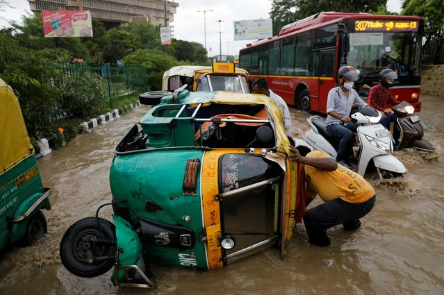 A man tries to pick an overturned auto rickshaw on a flooded street during heavy rains in New Delhi, India, August 19, 2020. (Photo by Adnan Abidi/Reuters)
