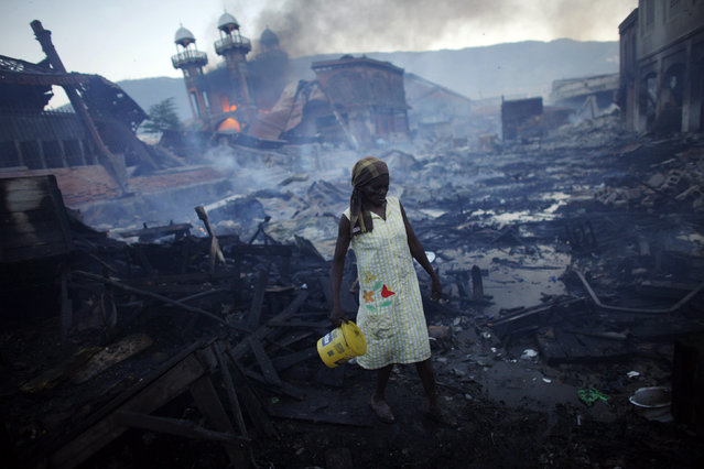 A woman walks near a fire at the Hyppolite iron market in downtown Port-au-Prince, Haiti, January 29, 2010. (Photo by Jorge Silva/Reuters)