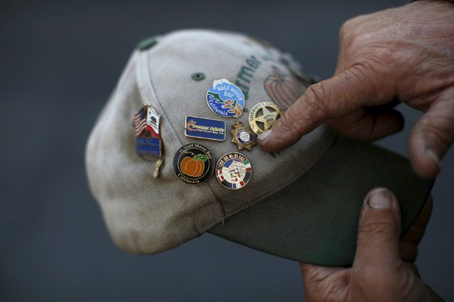 Farmer John, of Half Moon Bay, points to a collection of pins on his hat during the annual Safeway World Championship Pumpkin Weigh-off in Half Moon Bay, California October 12, 2015. (Photo by Stephen Lam/Reuters)