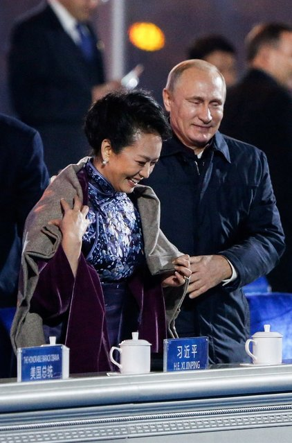 Russia's President Vladimir Putin (R) helps put a blanket on Peng Liyuan, wife of China's President Xi Jinping, as they watch a lights and fireworks show to celebrate Asia-Pacific Economic Cooperation (APEC) Leaders' Meeting, at National Aquatics Center, or Water Cube, in Beijing, November 10, 2014. (Photo by Reuters/Stringer)