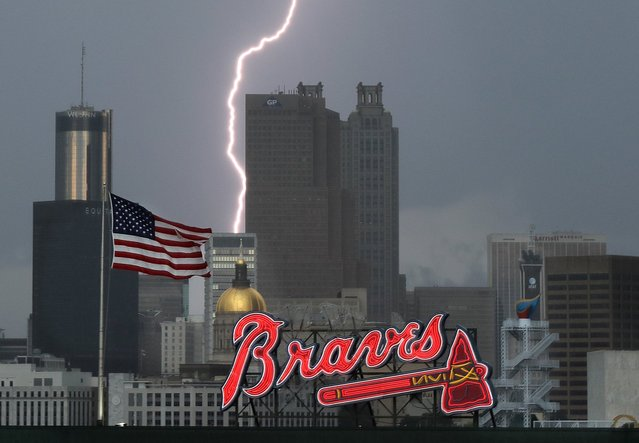 """A lightning storm moves through Atlanta before the Atlanta Braves play the Washington Nationals in a baseball game on Thursday, August 19, 2016, at Turner Field. The skyline of the city will change once the Braves move to Cobb County, leaving the """"Gold"""" dome and the Olympic ring and torch behind. (Photo by Curtis Compton/Atlanta Journal-Constitution via AP Photo)"""