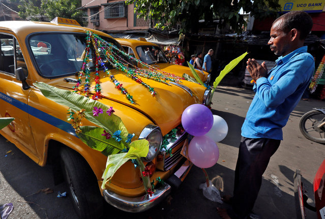 A taxi driver offers prayers to his car during the Vishwakarma Puja festival in Kolkata, India, September 17, 2016. (Photo by Rupak De Chowdhuri/Reuters)