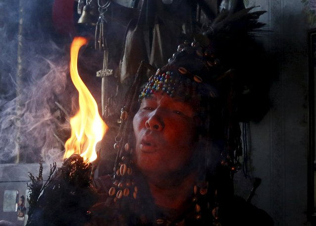 Yury Oorzhak, a shaman representing the so-called Adyg Eeren (Bear Spirit) society, conducts a session to clarify and predict the destiny of a customer, a local resident, at his residence in the town of Kyzyl, the administrative centre of Tuva region, Southern Siberia, Russia, October 7, 2015. (Photo by Ilya Naymushin/Reuters)