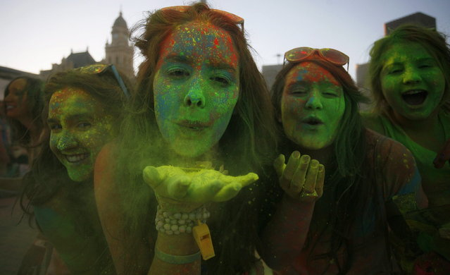 Revellers blow coloured cornflour powder as they take part in the Holi One festival in Cape Town, March 2, 2013. The event is inspired by the Hindu Holi spring festival of colour which originated in India. (Photo by Mark Wessels/Reuters)