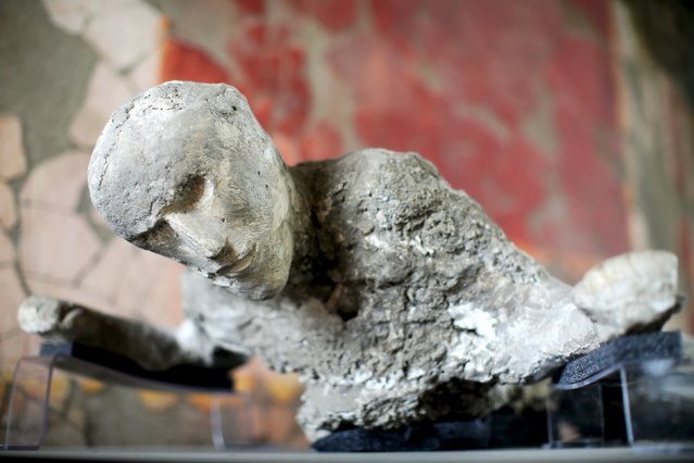 The plaster cast of a Pompeii victim lies in a frescoed room in the ancient Roman city, Pompeii, October 13, 2015. (Photo by Alessandro Bianchi/Reuters)