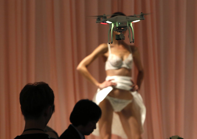 A videographer uses a drone as he takes a video of a model presenting a lingerie creation at the rehearsal for Eve's Temptation collection during China Fashion Week in Beijing, October 26, 2014. (Photo by Kim Kyung-Hoon/Reuters)
