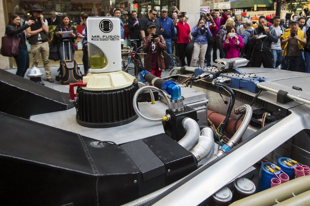 """Pedestrians stop to look at and photograph a DeLorean Motor Company DMC-12 customized to look identical to the car used in the film """"Back to the Future Part II"""" and that will be part of a Lyft promotion in New York, October 21, 2015. (Photo by Lucas Jackson/Reuters)"""