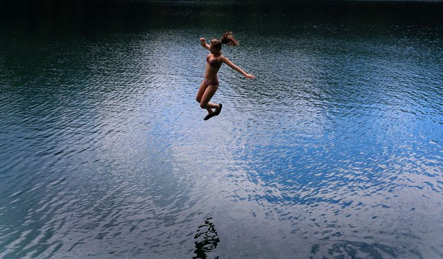 A young woman swings into the refreshing water of the Alatsee lake near Fuessen, southern Germany, on August 2, 2015. (Photo by Karl-Josef Hildenbrand/AFP Photo)