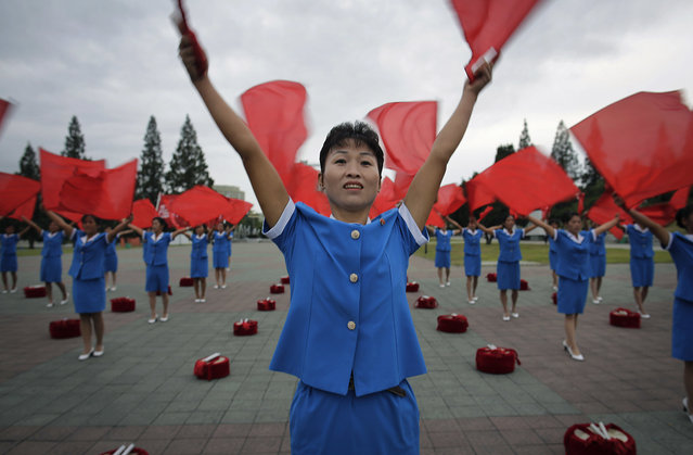North Korean women wave flags cheering on their fellow countrymen as they start their day during morning rush hour on Wednesday, September 28, 2016, in Pyongyang, North Korea. Women's League units are out in force these days in front of subway entrances and other strategic locations to dance and wave red flags as loud patriotic music blares from boom boxes. Sometimes they are joined by middle school brass bands in their morning ritual, which is intended to encourage workers to start their day off with more vigor. (Photo by Wong Maye-E/AP Photo)