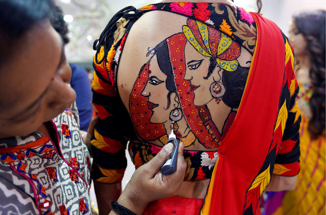 An artist applies final touches to a tattoo sketched on the back of a woman in preparations for the upcoming Navratri, a festival when devotees worship the Hindu goddess Durga and youths dance in traditional costumes in Ahmedabad, India, September 26, 2016. (Photo by Amit Dave/Reuters)