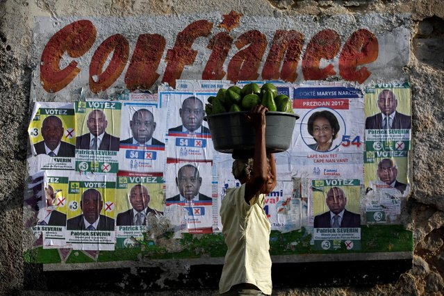 A woman carrying a bucket of avocados walks next to electoral posters on a street of Port-au-Prince, Haiti, September 12, 2016. (Photo by Andres Martinez Casares/Reuters)