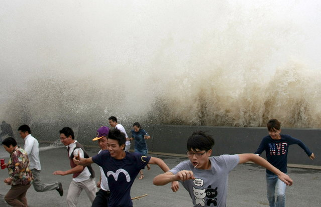 Visitors run away from a wave caused by a tidal bore which surged past a barrier on the banks of Qiantang River, in Hangzhou, Zhejiang province, China, September 15, 2015. (Photo by Reuters/China Daily)