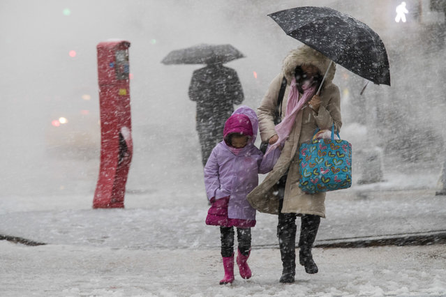 Pedestrians walk along Delancey St. during a snowstorm, Wednesday, March 7, 2018, in New York. The New York metro area was hit with another winter storm Wednesday just days after another nor'easter hammered the region with high winds. (Photo by Mary Altaffer/AP Photo)