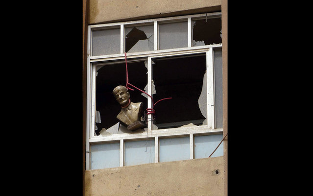 A bust of late Syrian President Hafez al-Assad, father of the current president Bashar al-Assad, is seen hung at a broken window of a building in Deir al-Zor April 2, 2013. (Photo by Khalil Ashawi/Reuters)