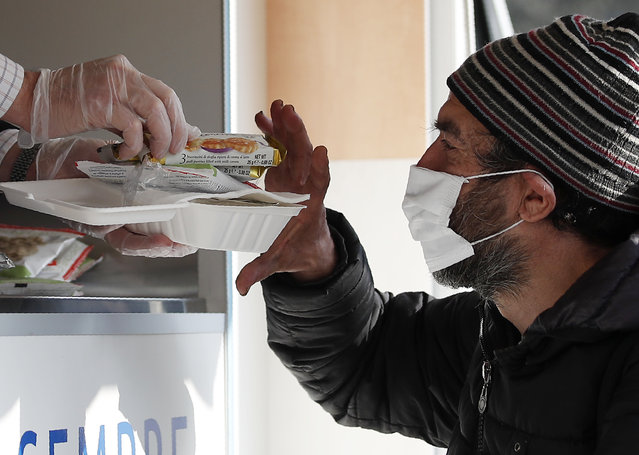 A volunteer serves food and drinks to a homeless man in Milan, Italy, Saturday, November 7, 2020. As the Italian government placed four regions, including hard-hit Lombardy, into effective lockdown for two weeks because infections and hospital saturation levels were rising fast, canteens and shelters for homeless people had to be shut down, leaving them with nowhere to get a meal. (Photo by Antonio Calanni/AP Photo)