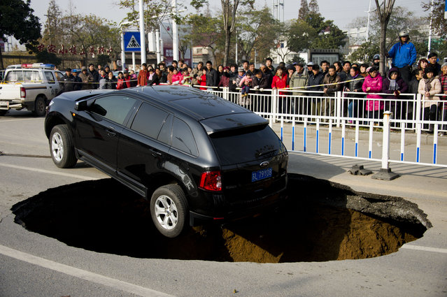 A Ford sedan car halts on the verge of a five meters wide and two meters deep hole at Yunlianghe Road on December 12, 2014 in Zhenjiang, Jiangsu Province of China. A Ford sedan car halted on the verge of a hole at Yunlianghe Road after the road collapsed and formed a five meters wide and two meters deep hole abound 8 o'clock on Friday morning. The road was just opened for two years and the reason is still under investigation.  (Photo by ChinaFotoPress/ChinaFotoPress via Getty Images)