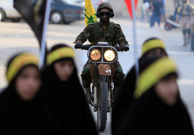 Muslim Shi'ite girls march as a Hezbollah member rides a motorbike during a procession ahead of the day of Ashura, in the Saksakieh village, in southern Lebanon, October 9, 2016. (Photo by Ali Hashisho/Reuters)