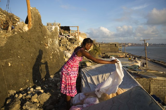 Andrenne Joseph dries her clothes near her destroyed house caused by Hurricane Matthew, in Jeremie,  Haiti. Saturday October 8, 2016. Aid has begun pouring into the hard-hit town,  where thousands of homes were damaged or destroyed and many people were running low on food and facing an increased risk for cholera. (Photo by Dieu Nalio Chery/AP Photo)