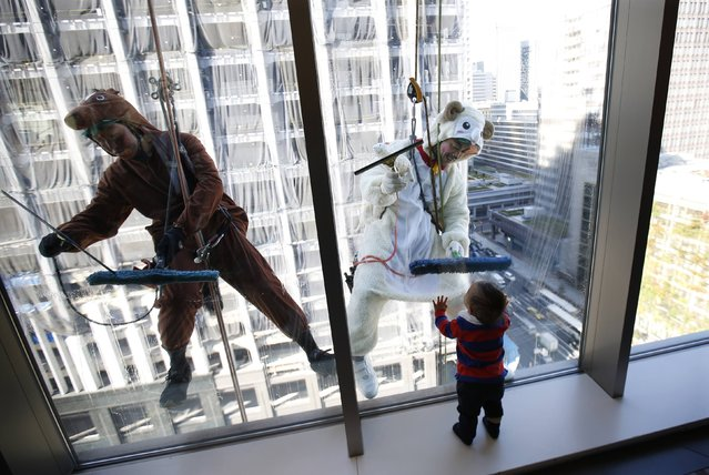 Window cleaners, dressed in horse (L) and sheep costumes featuring animal signs from the Chinese zodiac calendar, work during an event promoting the year-end and new year at a hotel in the business district of Tokyo December 19, 2014. (Photo by Issei Kato/Reuters)