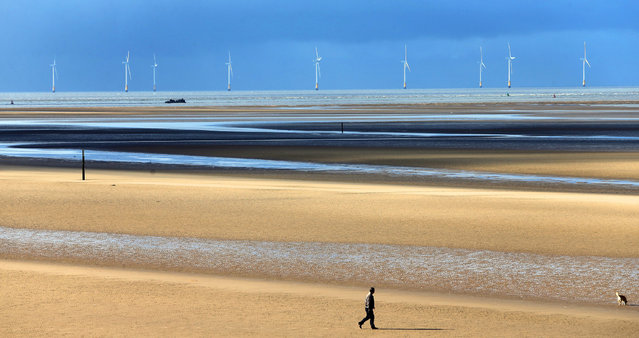 A man walks his dog along Formby Beach, Merseyside, as a shipwreck can be seen in the distance on March 24, 2015. (Photo by Peter Byrne/PA Wire)