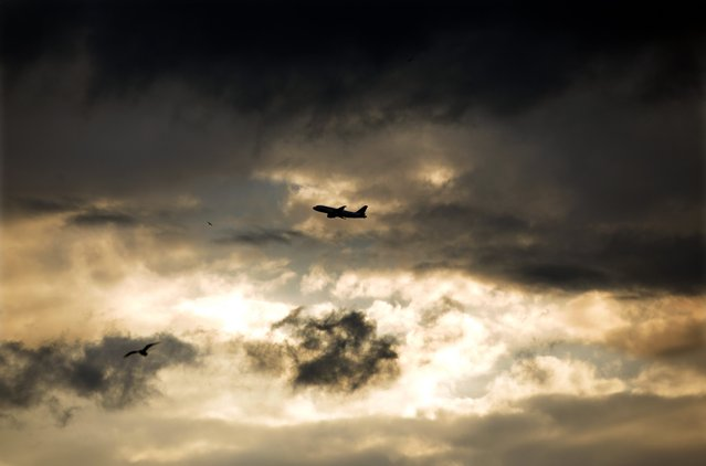 A passenger plane is silhouetted amongst the clouds, after heavy rains in southern France, as it flies above the Mediterranean Sea in Nice November 28, 2014. (Photo by Eric Gaillard/Reuters)