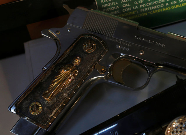 A gun decorated with gold is displayed in the Drugs Museum, used by the military to showcase to soldiers the lifestyles of Mexican drug lords, at the headquarters of the Ministry of Defense in Mexico City, October 14, 2016. (Photo by Henry Romero/Reuters)