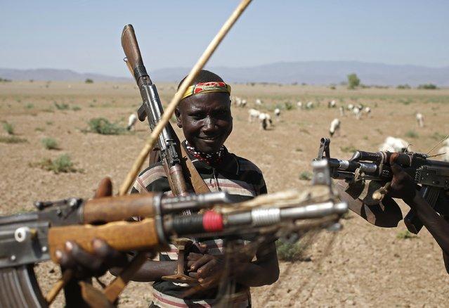 Turkana men carry rifles as they herd goats inside the Turkana region of the Ilemi Triangle, northwest Kenya December 21, 2014. (Photo by Goran Tomasevic/Reuters)